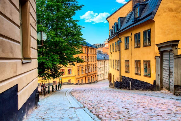 The narrow cobblestone street bastugatan in sodermalm with medieval houses in stockholm at summer sunny day. Premium Photo