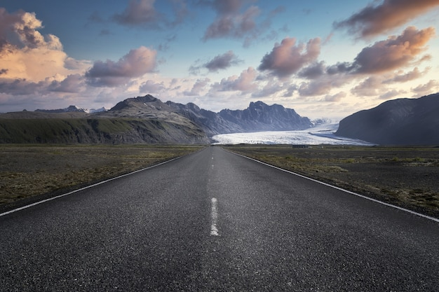 Narrow road leading to high rocky mountains in skaftafell national park in iceland Free Photo