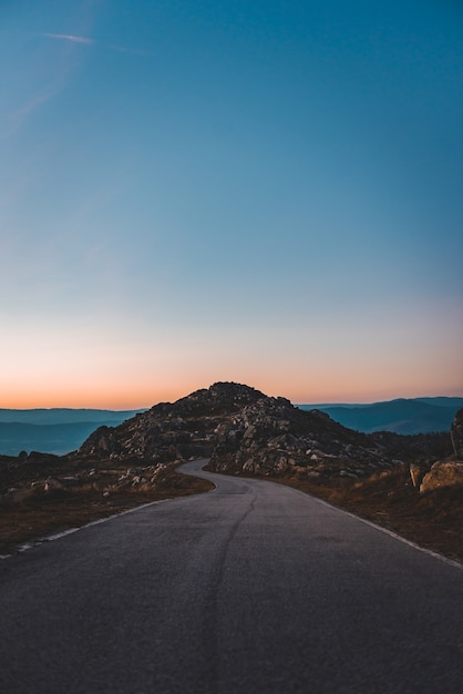 Narrow road leading to a rocky cave under the beautiful sunset sky Free Photo
