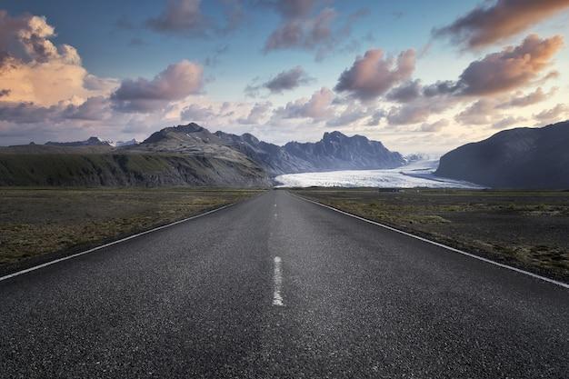 Узкая дорога, ведущая к высоким скалистым горам в национальном парке скафтафетль в исландии Бесплатные Фотографии