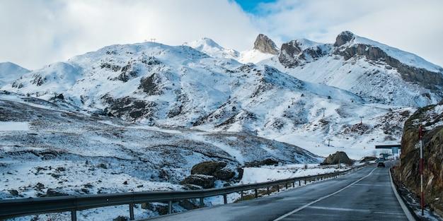 Узкая дорога в окружении высоких скалистых гор, покрытых снегом, под пасмурным небом Бесплатные Фотографии