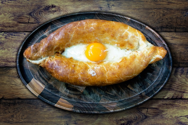 The national dish khachapuri on the board on the background of the old table, top view Premium Photo