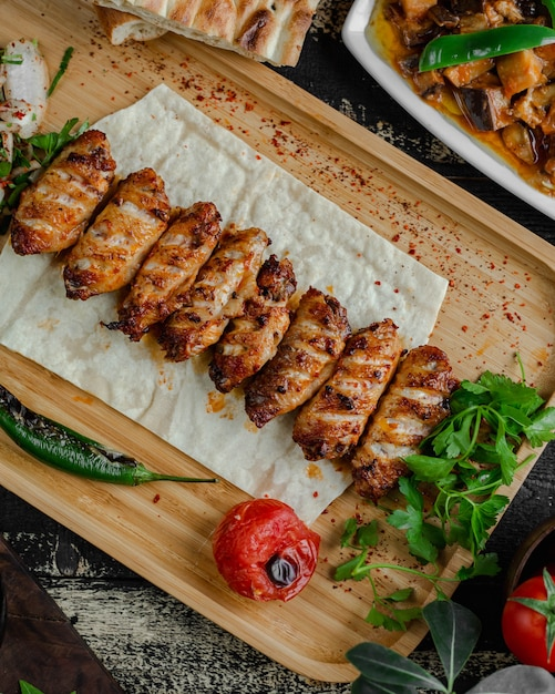 National meat barbecue kebab in lavash with parsley and grilled tomato. Free Photo