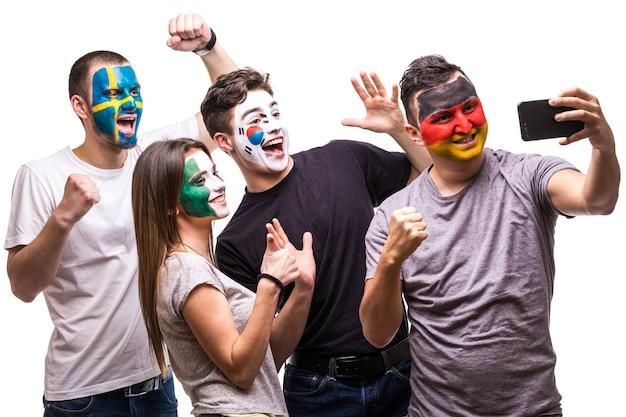 독일, 멕시코, 한국, 스웨덴의 국기 얼굴을 그린 국가 대표팀이 휴대 전화에서 셀카를 찍습니다. 무료 사진