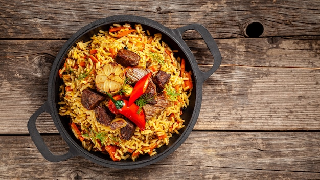 National uzbek pilaf with meat in a cast-iron skillet, on a wooden table. Premium Photo