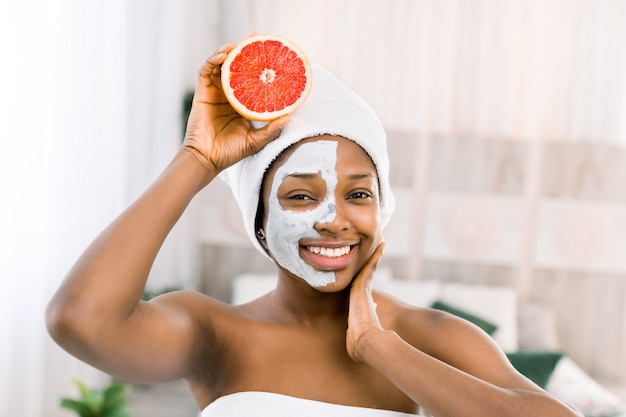Premium Photo | Natural beauty, spa and healthy skin concept. glad african  american woman in white towel, holds grapefruit, has toothy smile, with mud  mask on face