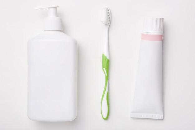 白い壁の歯磨き粉、歯ブラシ、クリームのボトルで分離された自然化粧品。美容コンセプト。衛生 無料写真