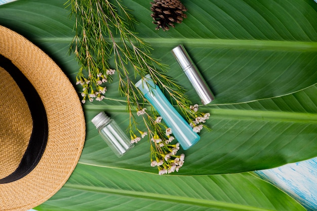 Natural cosmetics bottle containers on green leaf background Premium Photo