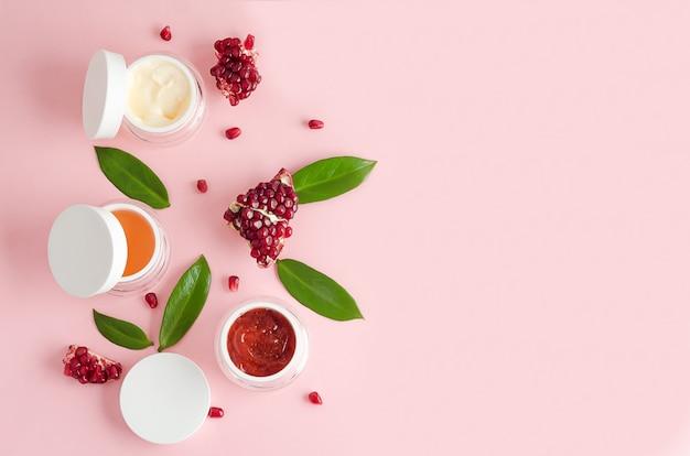 Натуральная косметика с фруктовыми кислотами aha, экстрактом граната на розовом фоне. концепция красоты. баночка с кремом, маской, скрабом, пилингом для профессионального ухода за кожей лица. баннер, макет, копия пространства Premium Фотографии