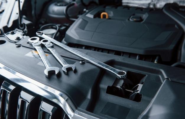 Естественный дневной свет. инструменты для ремонта, лежа на двигателе автомобиля под капотом Бесплатные Фотографии