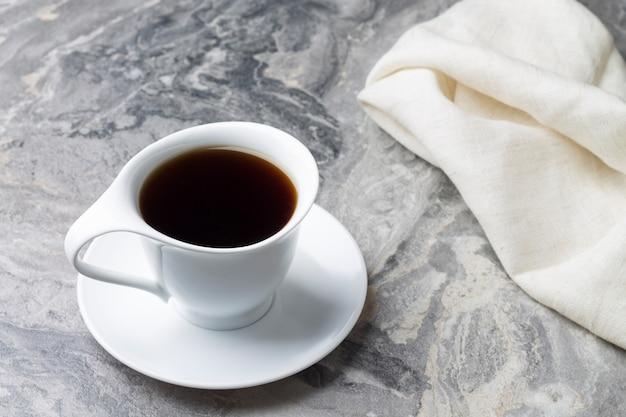 Натуральный напиток цикорий в белой чашке с блюдцем на мраморном фоне. Premium Фотографии