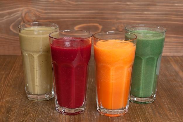 カボチャ、ビート、リンゴの天然フレッシュジュースと木製のテーブルにスピルリナの飲み物 Premium写真