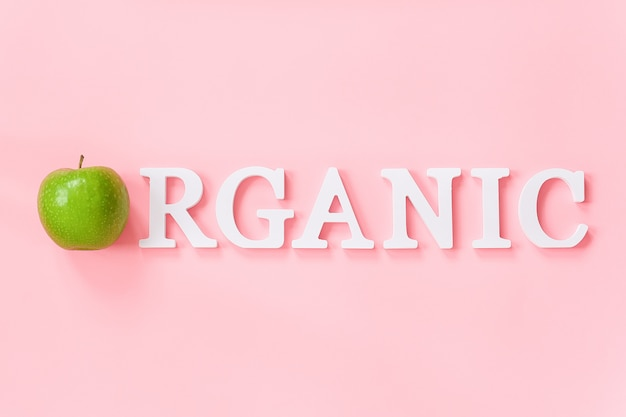 Natural green apple and text organic from volume white letters. creative concept organic natural fruits food Premium Photo