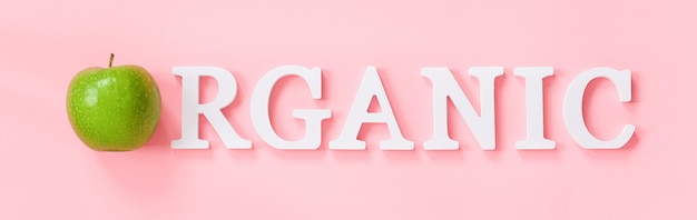 Natural green apple and text organic from volume white letters on pink wall Premium Photo