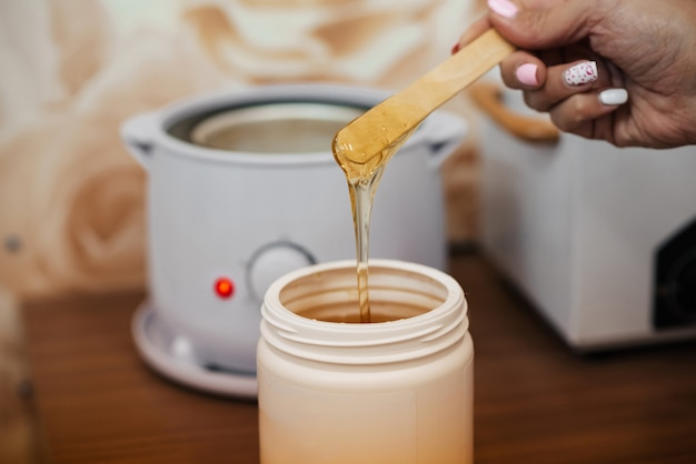 Natural hot sugar paste for depilation in a jar and on a wooden spatula in the hands of a woman beautician Premium Photo