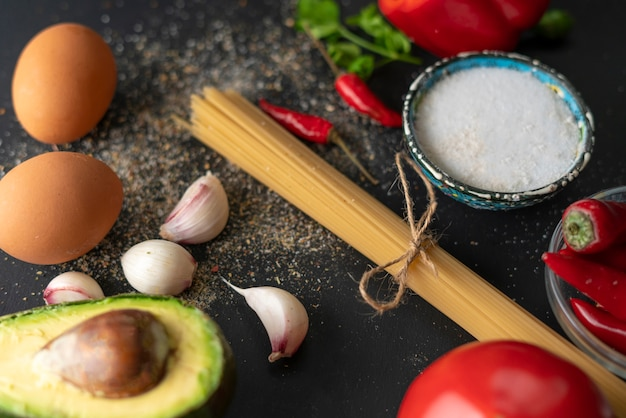 Natural ingredients for cooking pasta, raw spaghetti tied up with a rope, salt and pepper on the tables Premium Photo