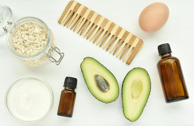 Натуральные ингредиенты для ухода за волосами, авокадо, овес, яйцо, йогурт, эфирные масла, домашняя маска для волос. Premium Фотографии