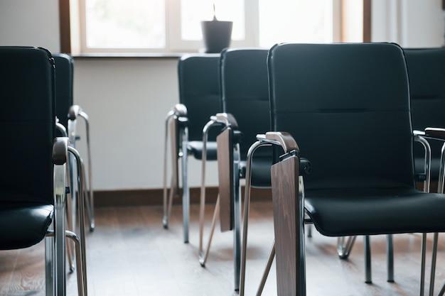 Illuminazione naturale. aula aziendale durante il giorno con molte sedie nere. pronto per gli studenti Foto Gratuite