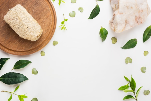 Natural loofah on wooden board with spa stone and spread leaves on white background Free Photo