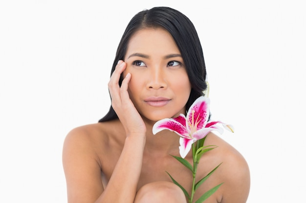 Natural model posing with lily and touching her face Premium Photo