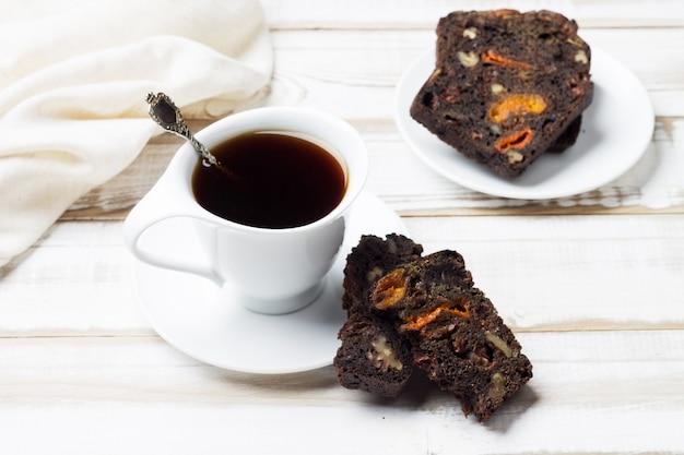 Натуральный утренний напиток из цикория в белой чашке и блюдце с кусочками фруктово-орехового хлеба. Premium Фотографии