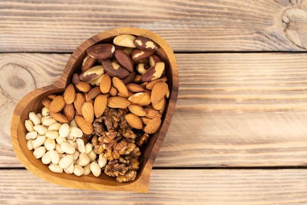 갈색 나무 테이블에 심장 기호 모양의 나무 접시에 다양한 견과류의 자연 영양 조화 프리미엄 사진