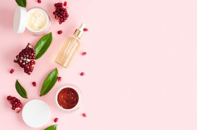 Натуральная органическая косметика с фруктовыми кислотами aha, экстрактом, гранатовым маслом на розовом фоне. концепция красоты. флакон, баночка с кремом, маска, скраб, пилинг для ухода за кожей лица. копировать пространство, мягкий фокус Premium Фотографии