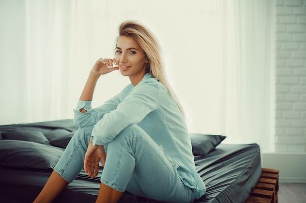 Natural pretty blonde sitting on bed Premium Photo