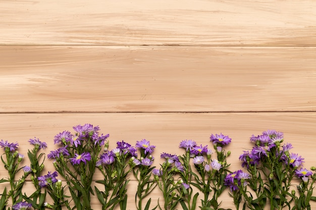 Natural purple flowers on wooden background Free Photo