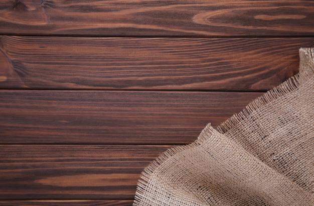 Естественная вретище на коричневом деревянном. холст на коричневом деревянном столе Premium Фотографии