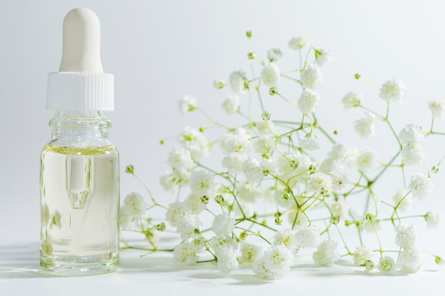 Natural serum in cosmetic bottle with dropper. organic spa cosmetics with herbal ingredients. Premium Photo