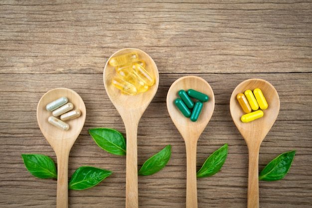 Natural supplements in capsule,from herbs on wood Premium Photo