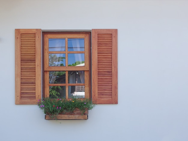 Natural Wood Windowwith Hanging Flower Decor On Cement Wall Photo