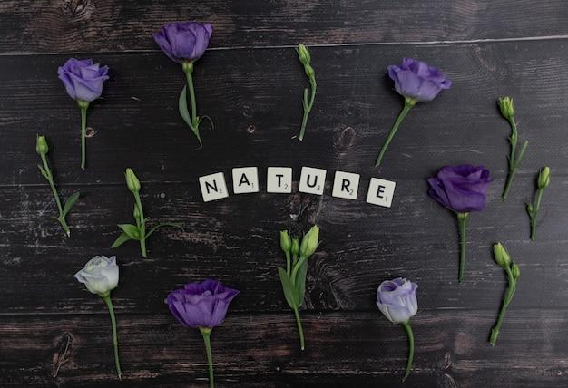 나무 표면에 보라색 Lisianthus 꽃으로 둘러싸인 스크래블 블록으로 만든