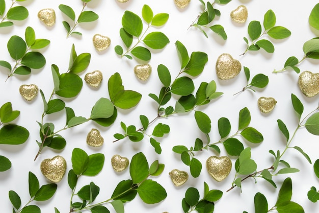 Nature pattern made with green plant branches and golden sparkling hearts on white surface Premium Photo