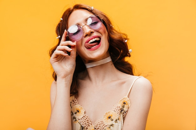 Naughty woman in lilac sunglasses is licking her lips and posing on orange background. Free Photo