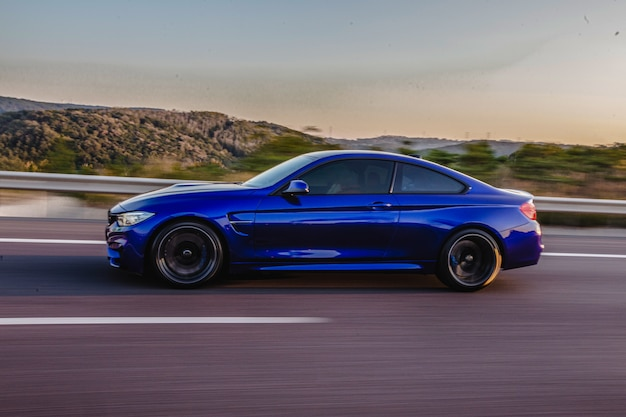 Navy blue sport coupe on the road, side view. Free Photo