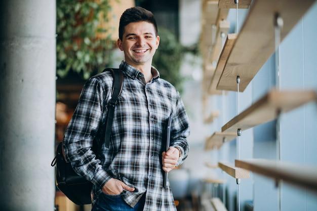 電話で話しているウィンドウndを立っているカフェの若い男 無料写真