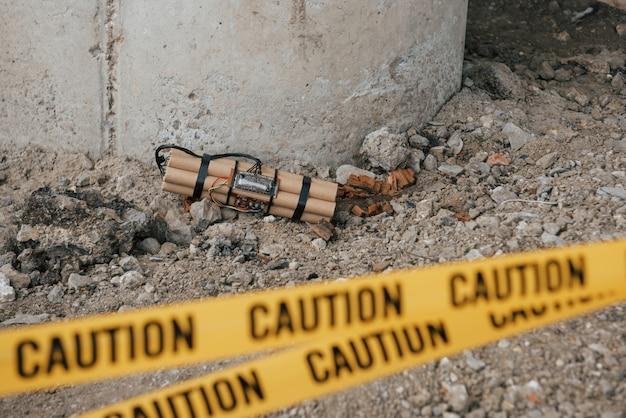 橋のサポートに近い。地面に横たわっている危険な爆発物。前に黄色の注意テープ 無料写真