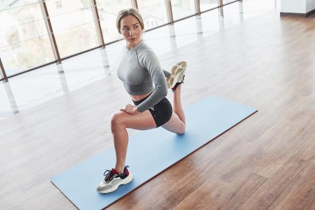 Возле большого окна. спортивная молодая женщина имеет фитнес-день в тренажерном зале в утреннее время Бесплатные Фотографии