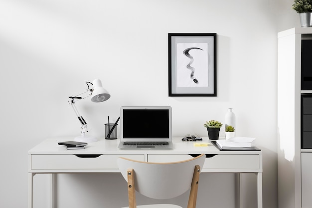 Опрятное и организованное рабочее место со стулом и лампой Бесплатные Фотографии