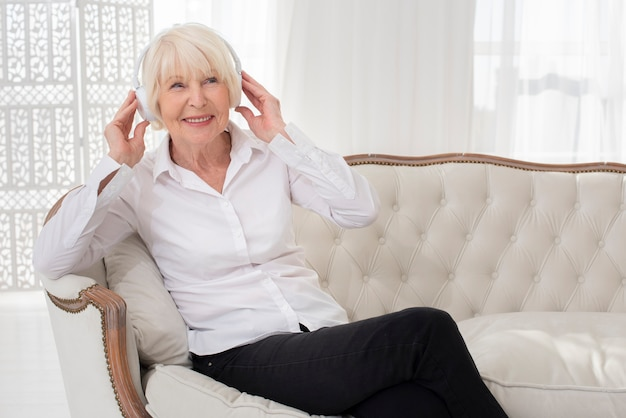 Neat Old Woman Sitting On Sofa With Headphones Free Photo