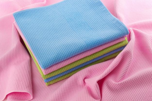Аккуратно сложенные полотенца лежат на мятом полотенце. Premium Фотографии