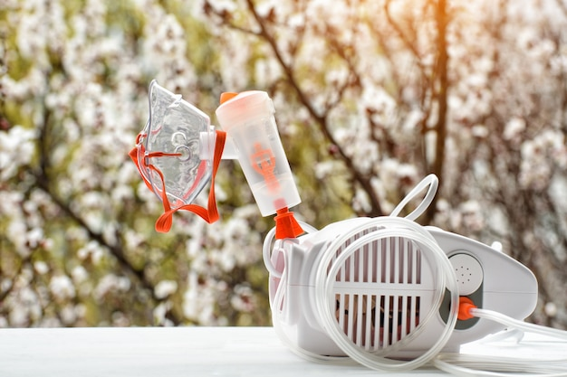 Nebulizer with a mask on the  of a blossoming tree. spring exacerbation Premium Photo