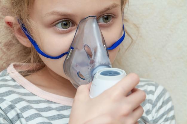Маленькая девочка делая ингаляцию с nebulizer дома. маленькая девочка с ингалятором. макрофотография, выборочный фокус Premium Фотографии