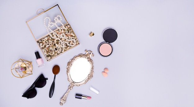 Necklace and flowers in the box; lipstick; blender; sunglasses; oval comb; compact powder; lipstick and hand mirror on purple background Free Photo