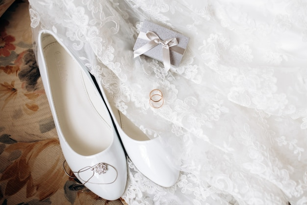 Necklace, white shoes and wedding rings on the wedding dress Free Photo
