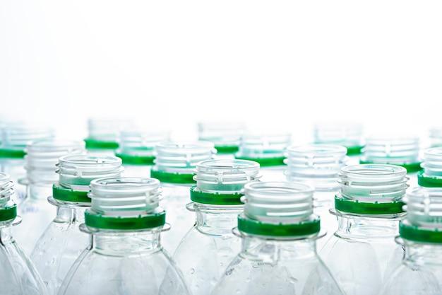 Горлышки пластиковых бутылок без крышек на белом фоне. концепция производства пластиковых бутылок Premium Фотографии