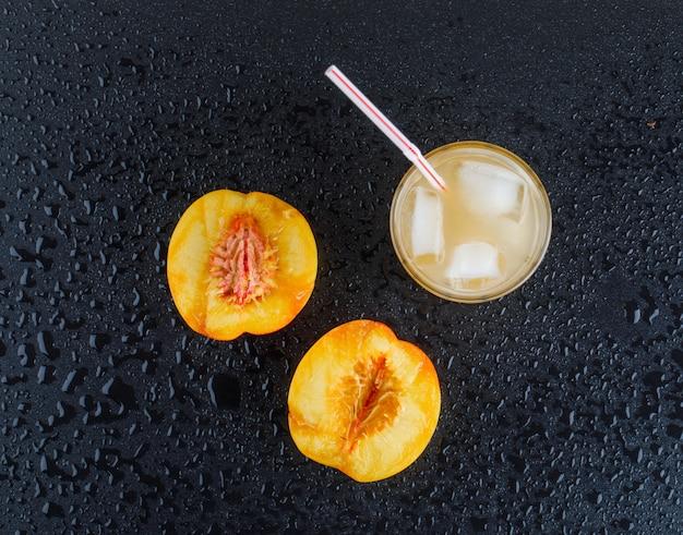 アイスジュースフラットネクタリンスライスを濃い灰色の表面に置く 無料写真