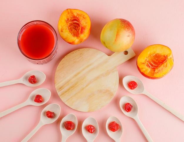ネクタリンジュース、ピンクのドライチェリー、まな板のテーブル、フラットレイアウト。 無料写真